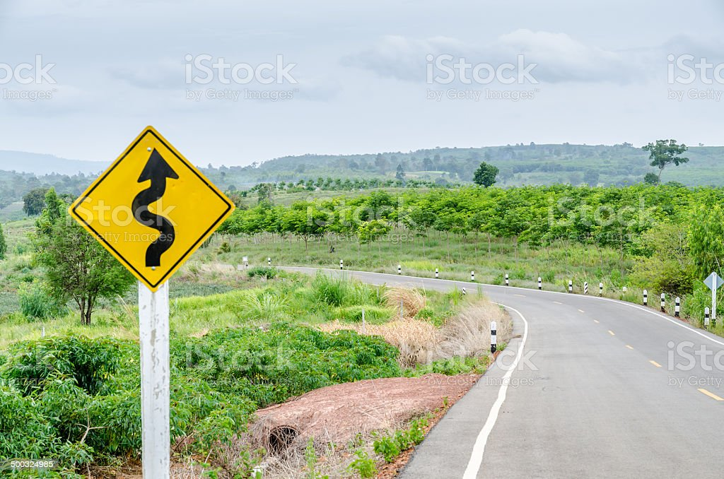 Twisty road with roadsign in nature stock photo
