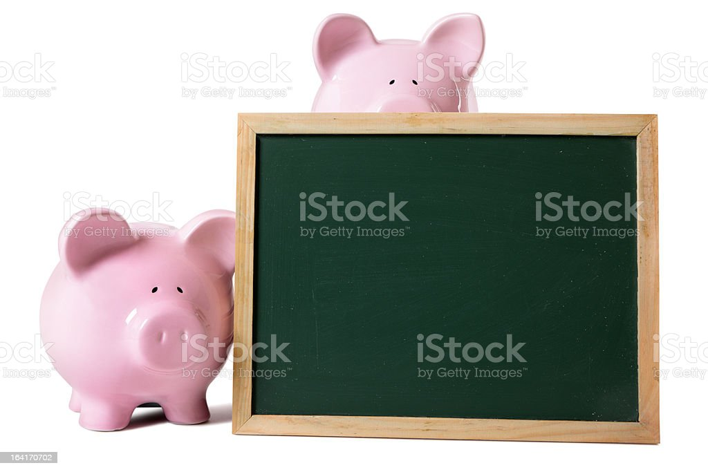 Two 3D cartoon of piggy banks by a blank chalkboard royalty-free stock photo
