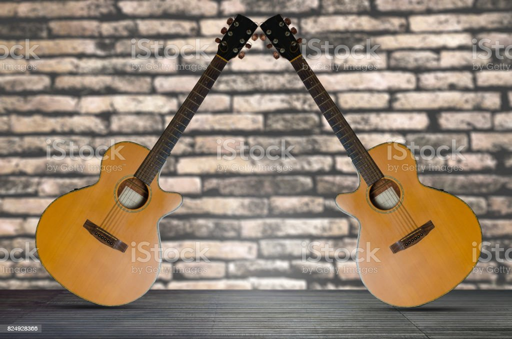 two acoustic guitar on the wooden floor against  brick wall background. stock photo