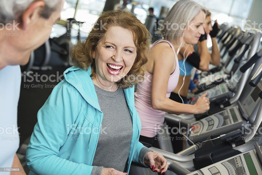 Two active seniors exercising on treadmills in a gym. royalty-free stock photo