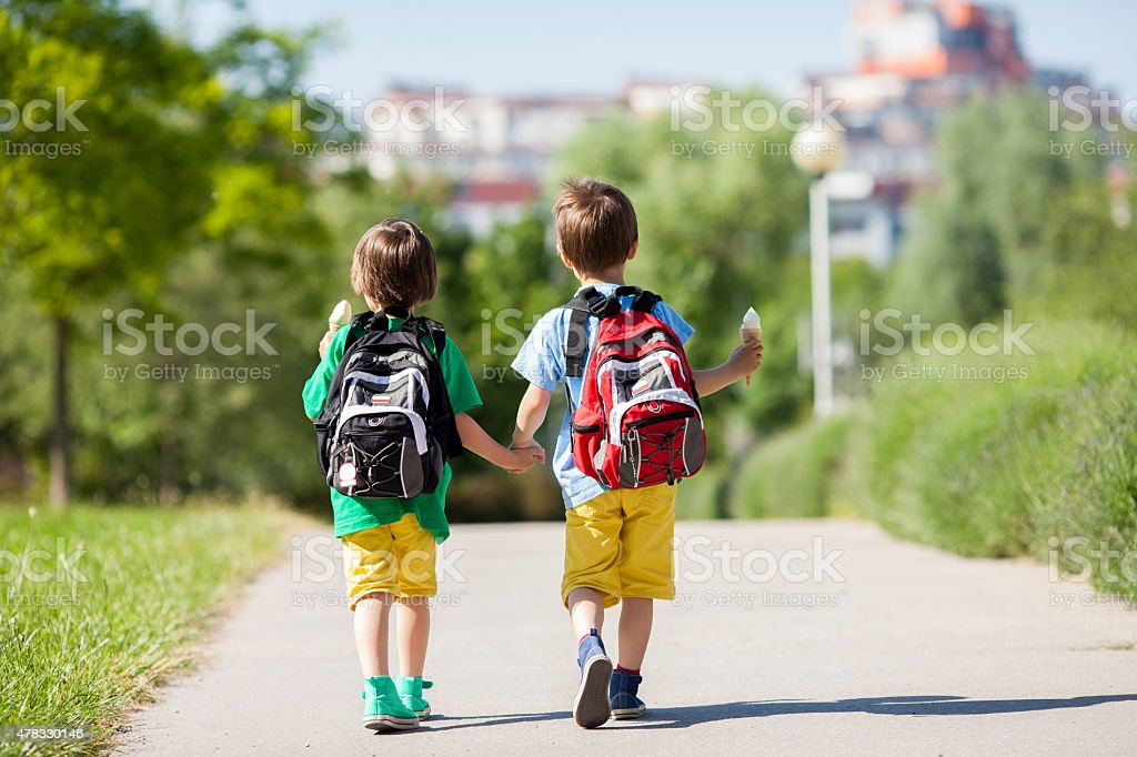 Two adorable boys in colorful clothes and backpacks, walking awa stock photo