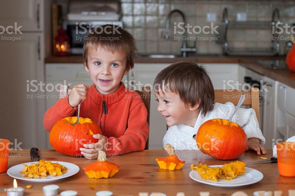 Two adorable boys, preparing jack o lantern for Halloween stock photo
