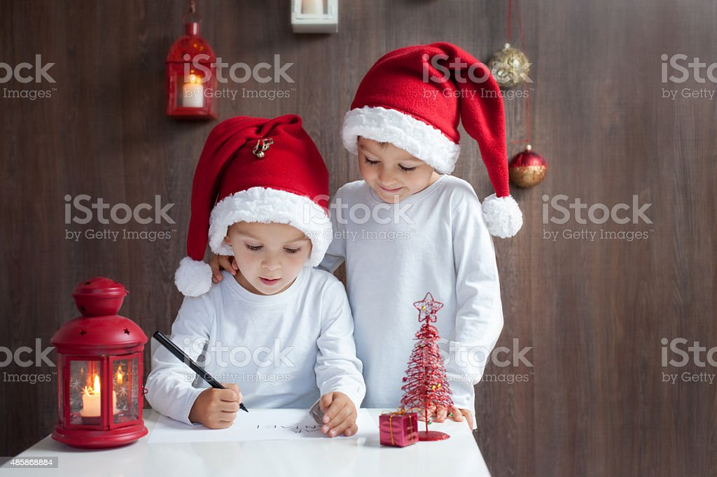 Two adorable boys, writing letter to Santa stock photo
