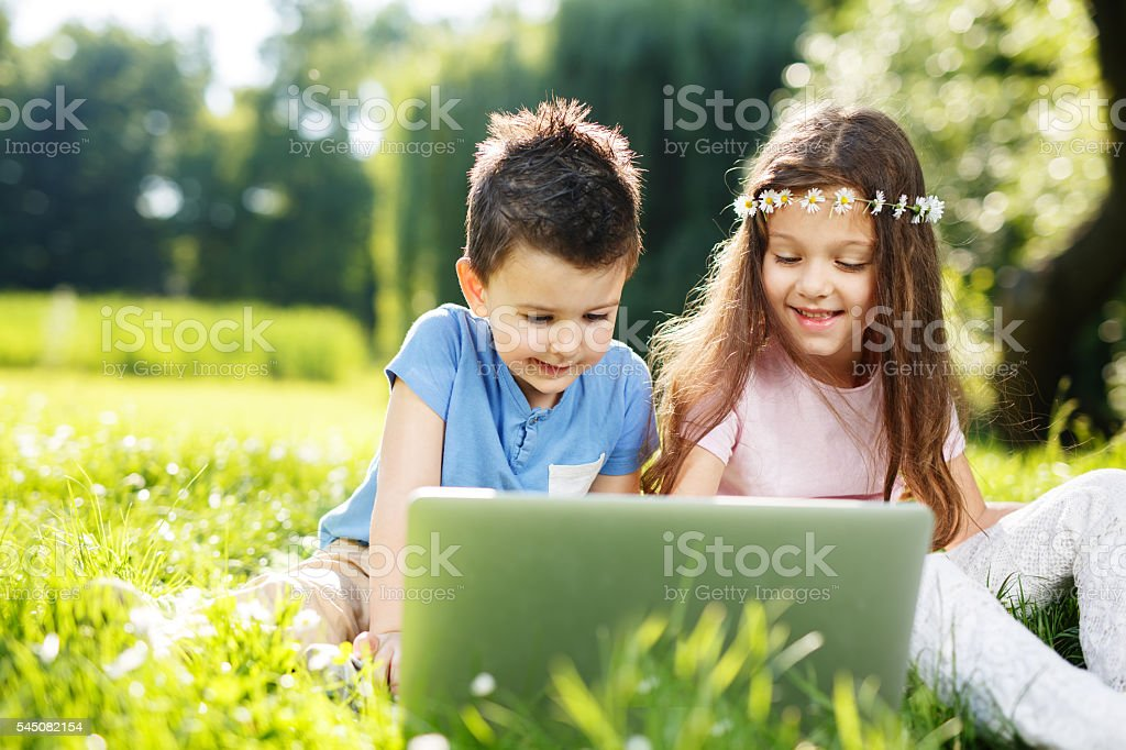 Two adorable children using laptop computer outdoor. stock photo