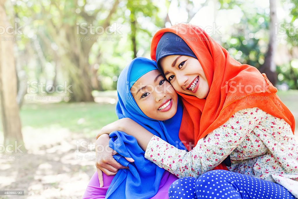 two adorable indonesian muslim sisters stock photo