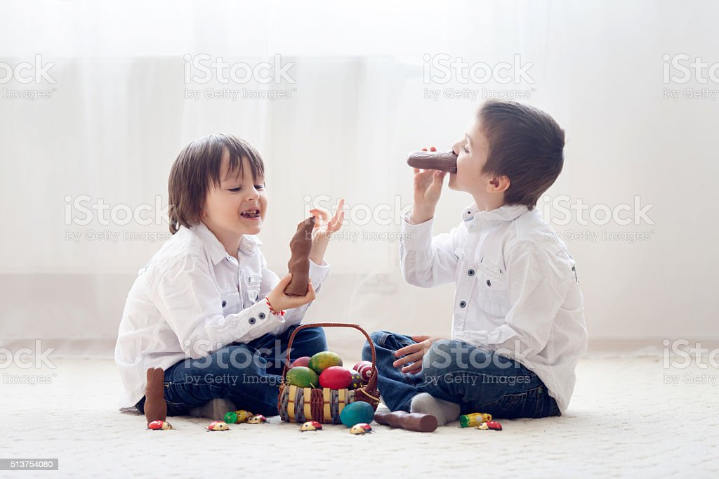 Two adorable little children, boy brothers, having fun eating ch stock photo