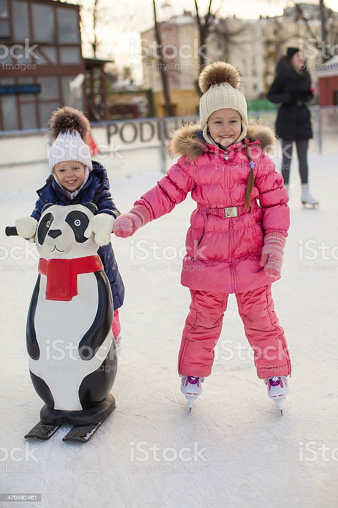 Two adorable little girls skating at the ice-rink stock photo