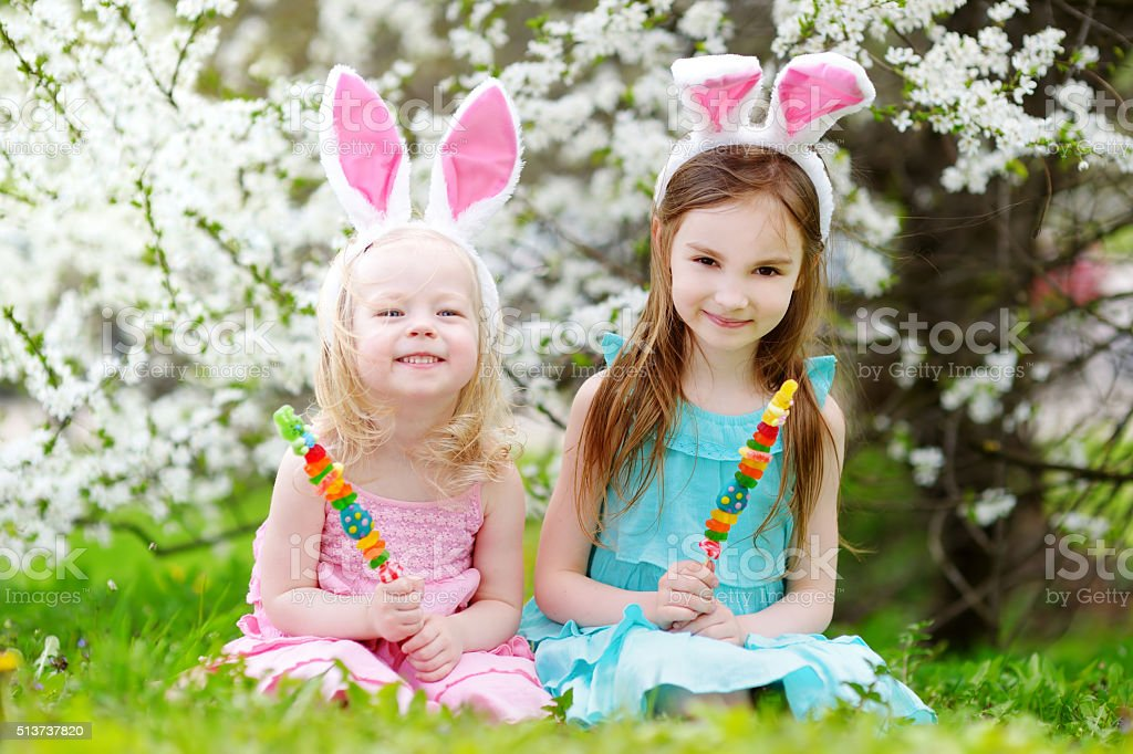 Two adorable little sisters eating colorful gum candies on Easte stock photo