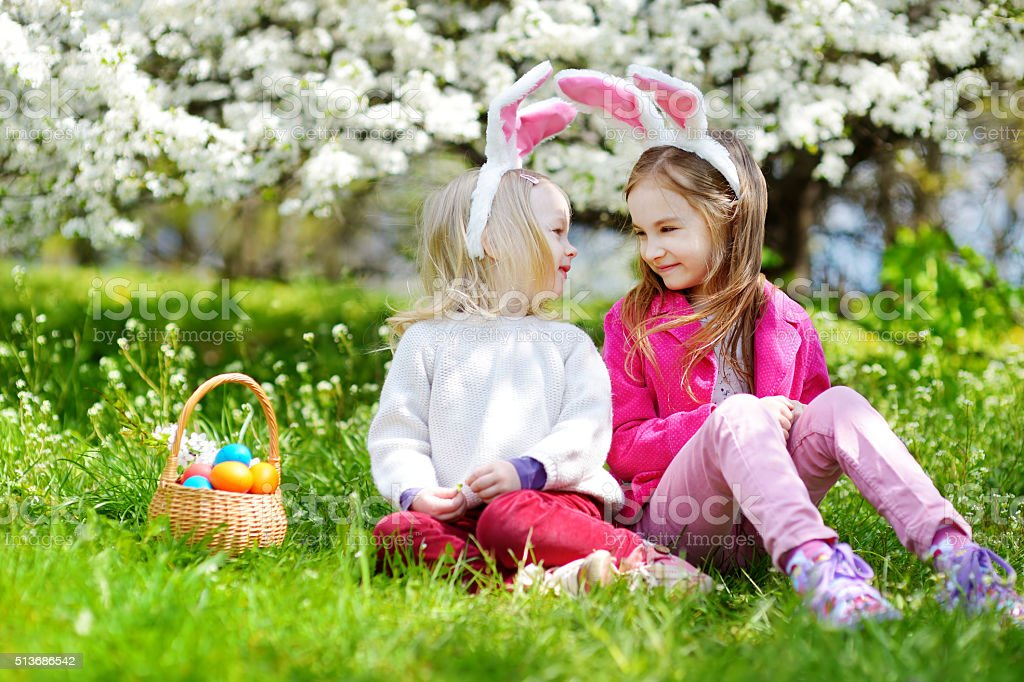 Two adorable little sisters playing with Easter eggs on Easter stock photo