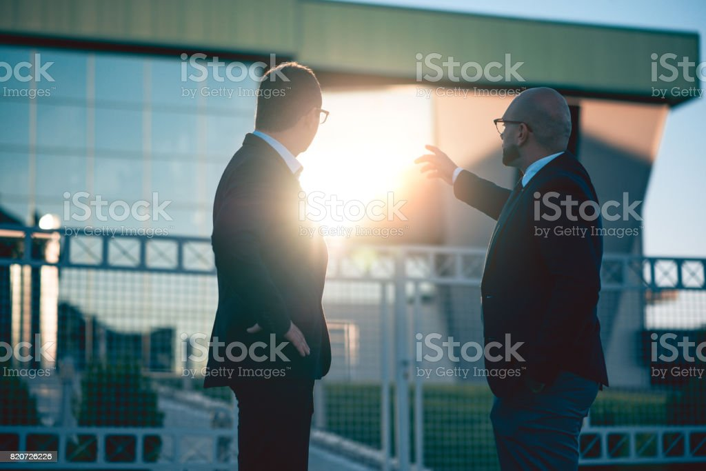 Two Adult Businessmen Discussing and Pointing in front of New Office Building stock photo