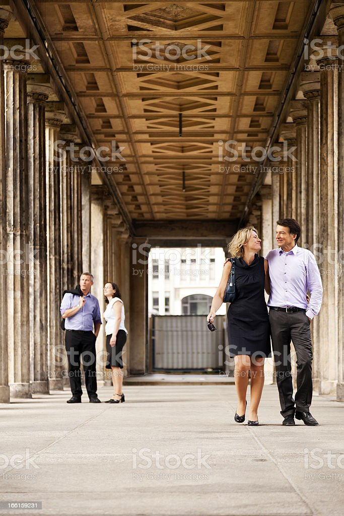 Two Adult Couples Walking in Columns Passage royalty-free stock photo