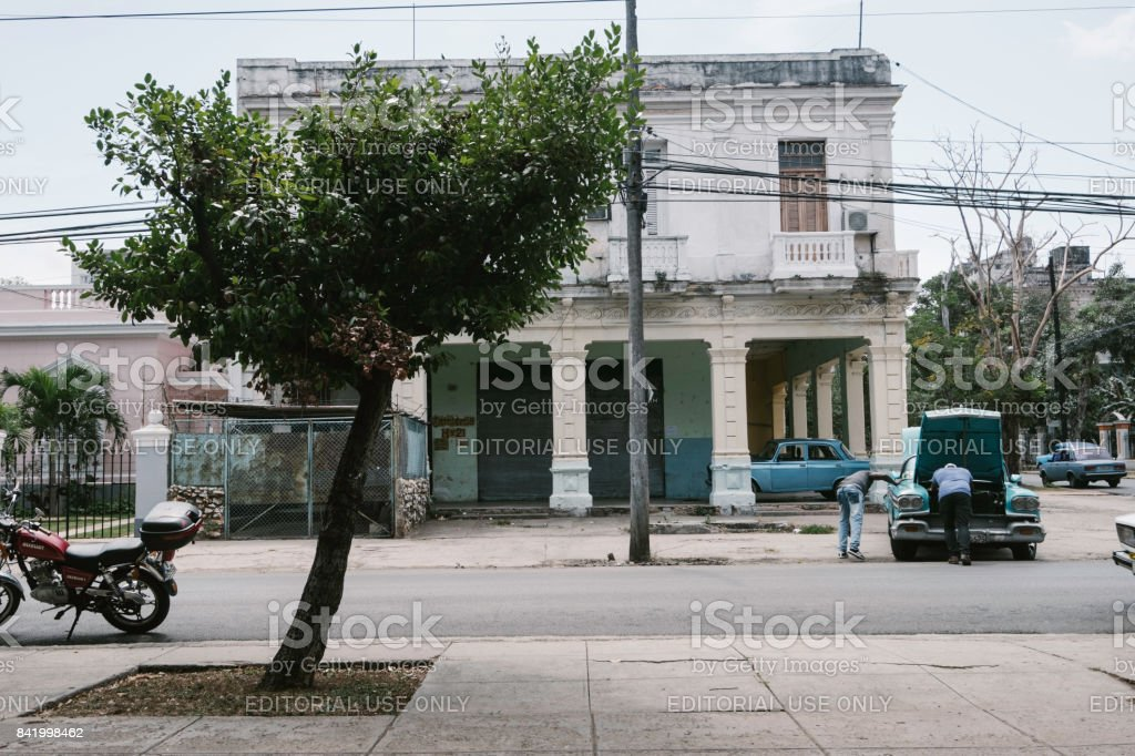 Two adult men work on a classic blue car on the streets of Havana stock photo