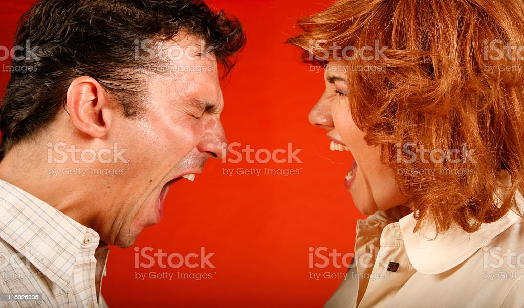 Two adults by a red wall yelling in the midst of quarrel royalty-free stock photo