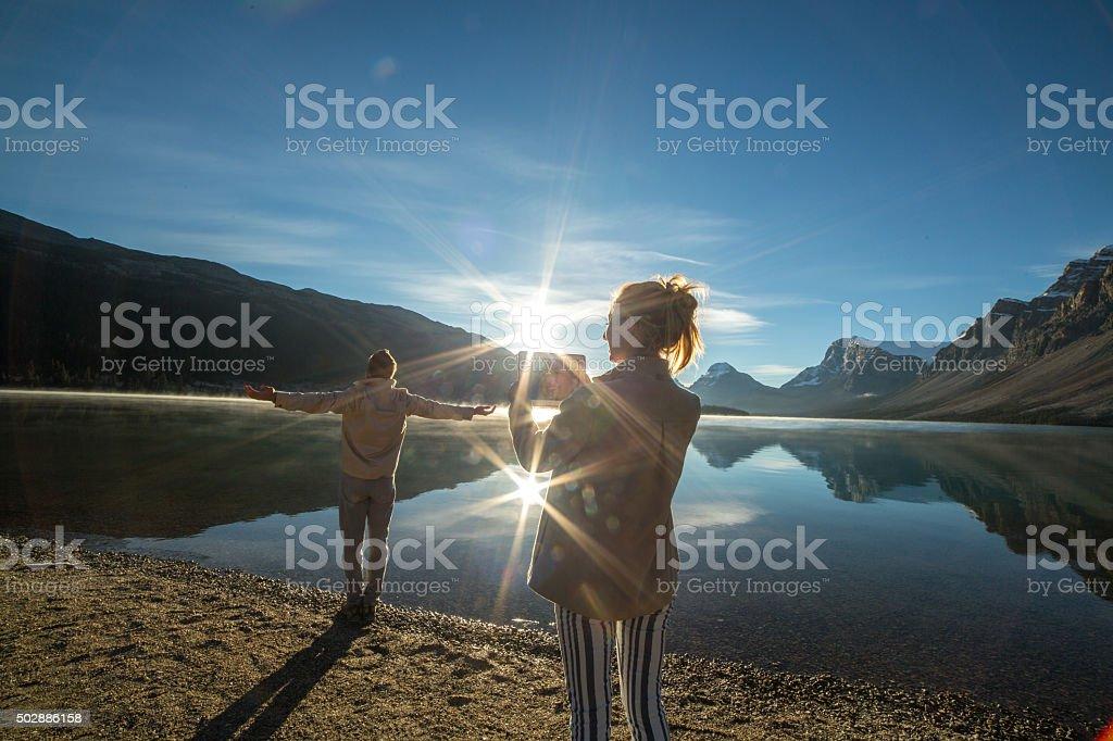 Zwei Erwachsene am See bei Sonnenaufgang mit digitalen tablet – Foto