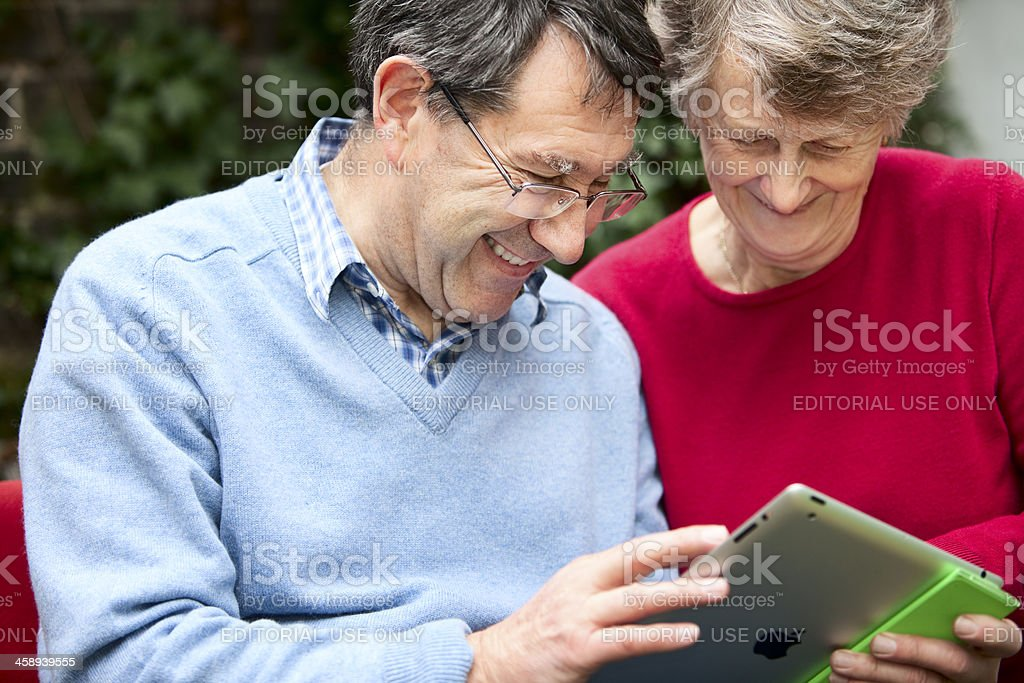 Two adults looking at the screen of an IPad2 laughing royalty-free stock photo