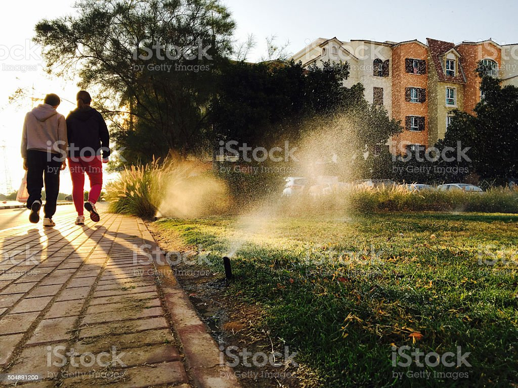 Two Adults walking on society footpath - Healthy Lifestyle stock photo
