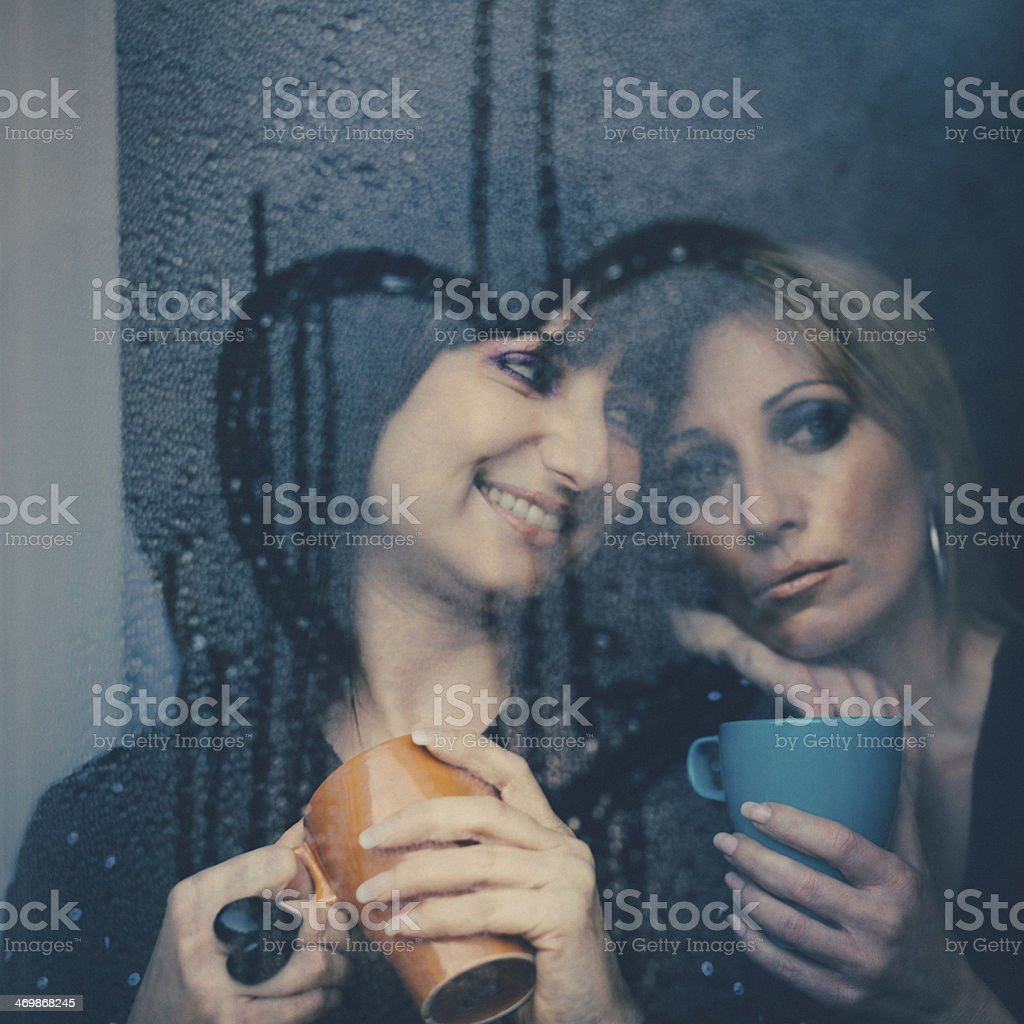 Two affectionate women behind a window stock photo