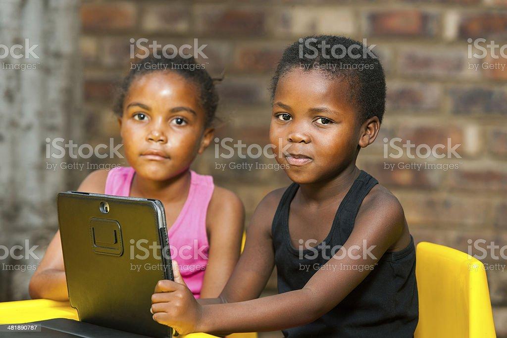 Deux enfants africains avec tablette et mur de briques photo libre de droits