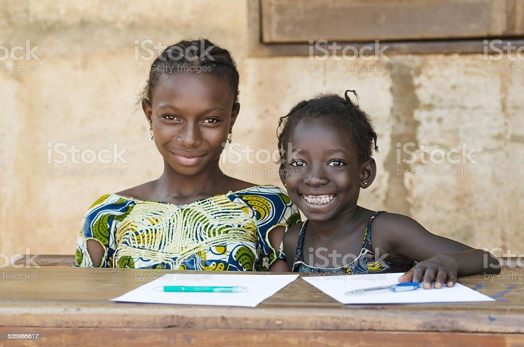 Two African Ethnicity Children Smiling Studying in a School Environment stock photo