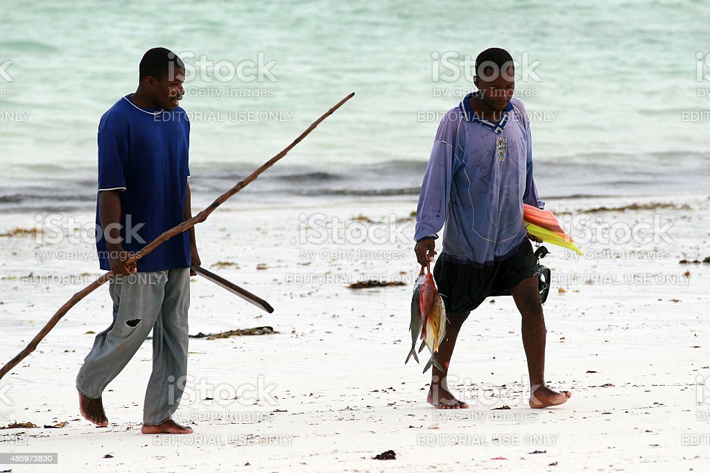 Two African fisherman divers return home with their catch. stock photo