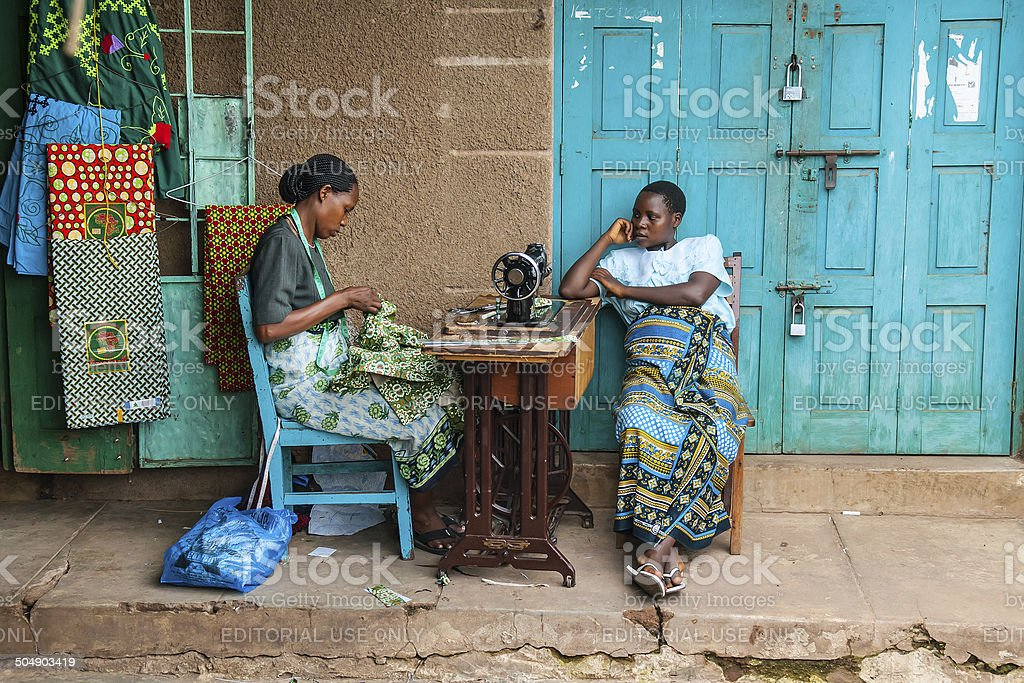 Two African woman sitting next to sewing machine stock photo