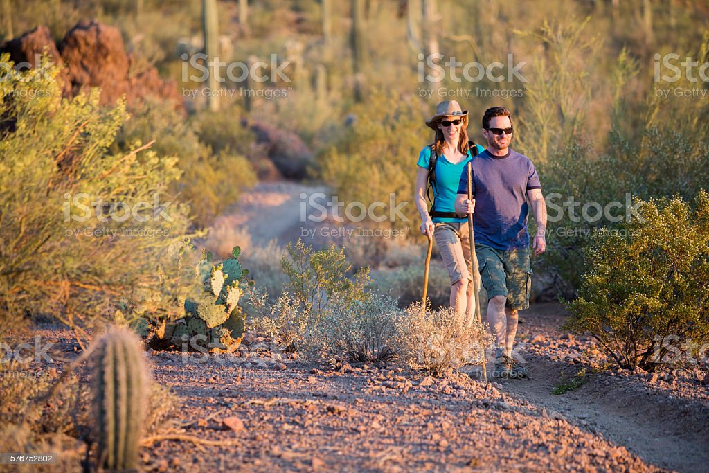 Two Afternoon Hikers on Rugged Desert Trail stock photo