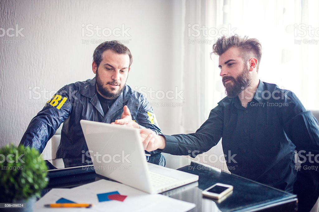 Two agents looking at laptop stock photo