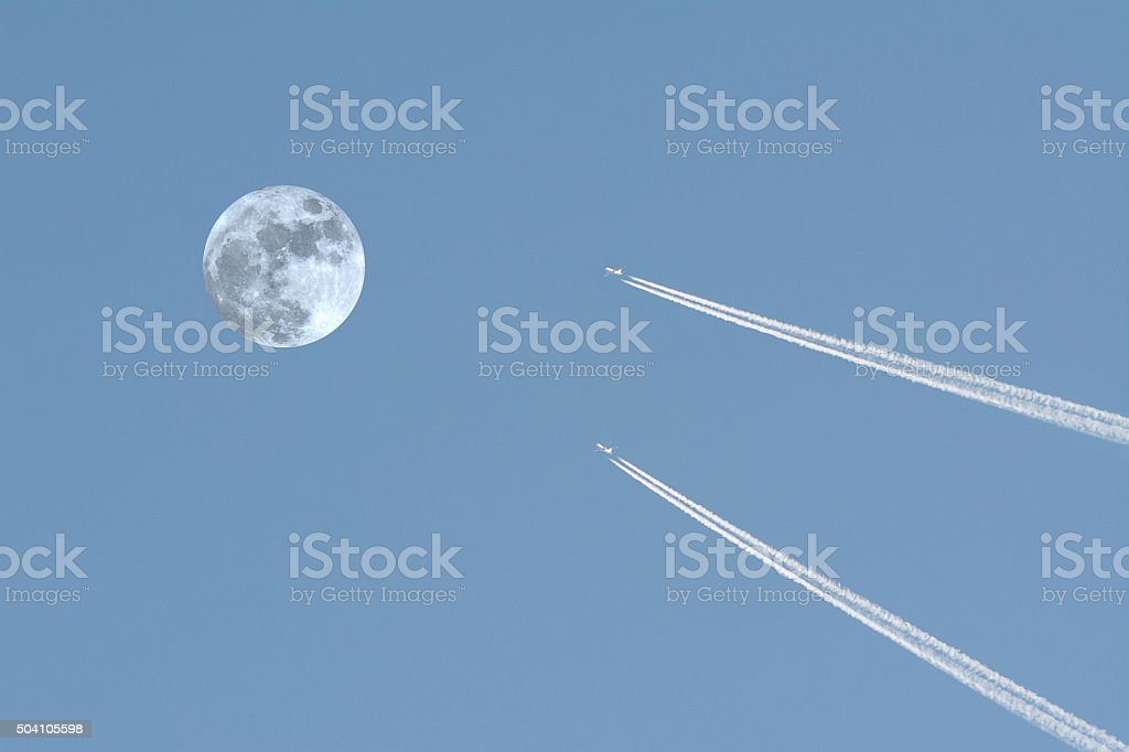 Two airplanes crossing the moon stock photo