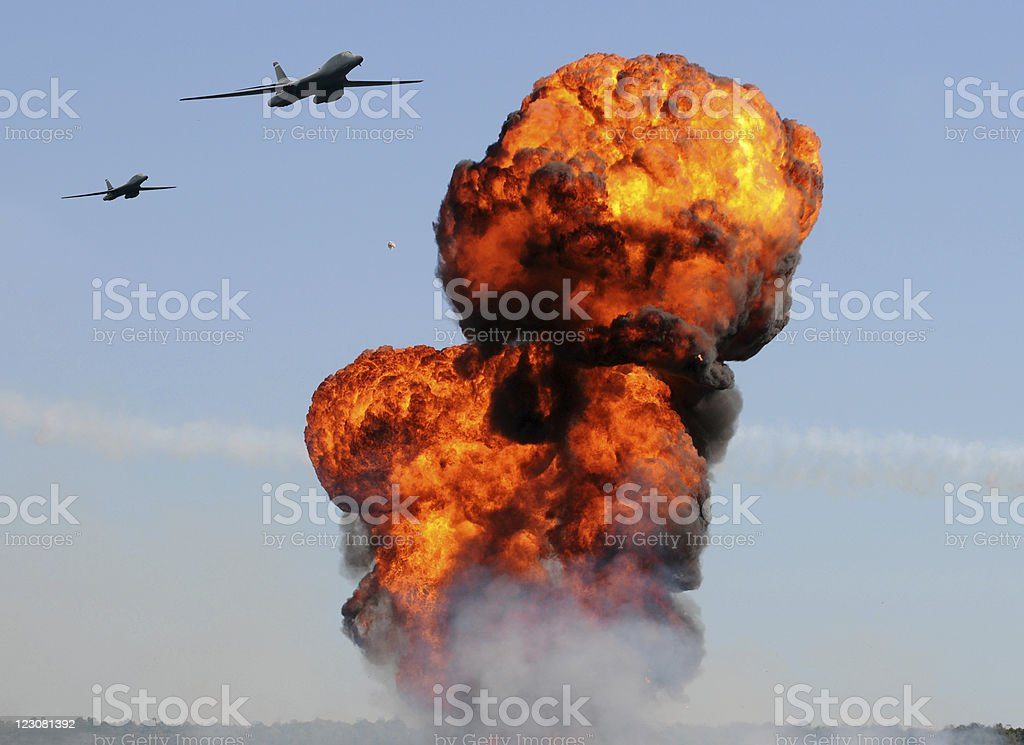 Two airplanes flying towards an explosion in a blue sky stock photo