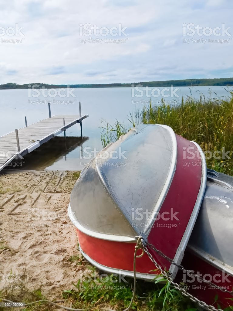Two aluminum boats pulled up on shore with a dock in the background stock photo