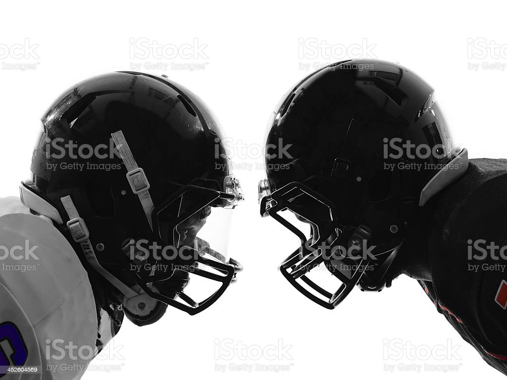 two american football players facing eachother silhouette stock photo