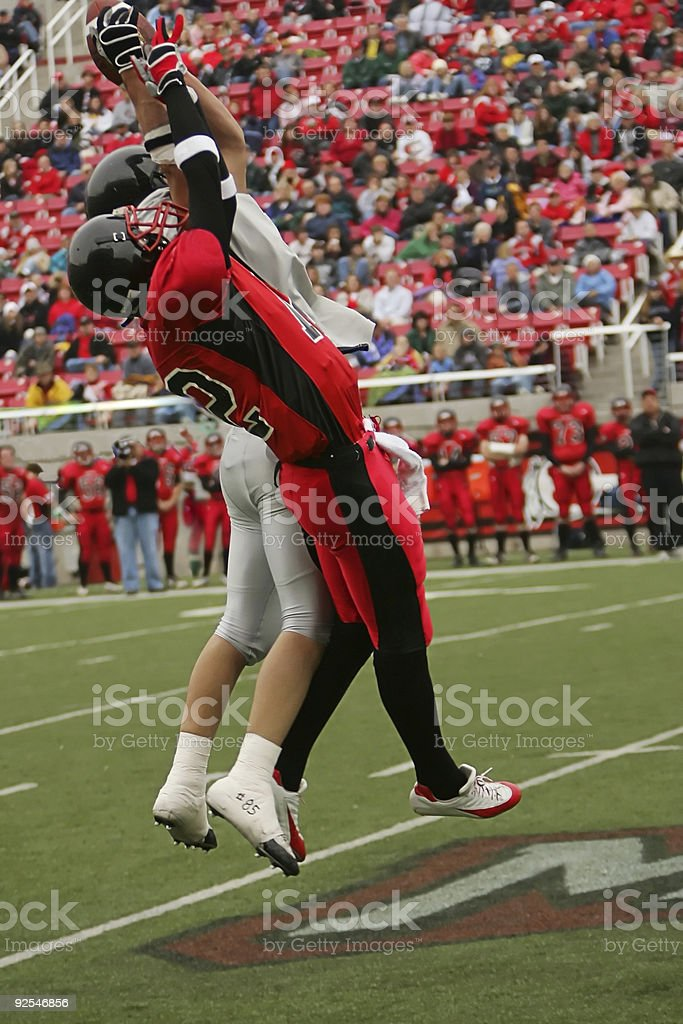 Two American Football Players Jump for Airborne Ball stock photo