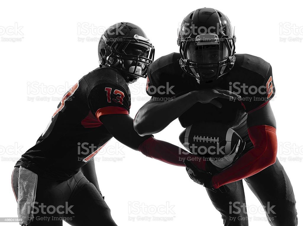 two american football players passing play action silhouette stock photo