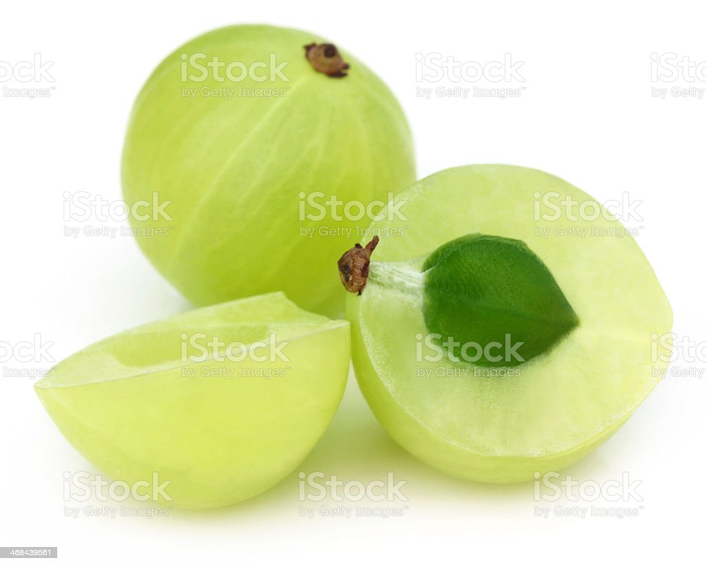 Two amla fruit on a white background, one sliced in half stock photo
