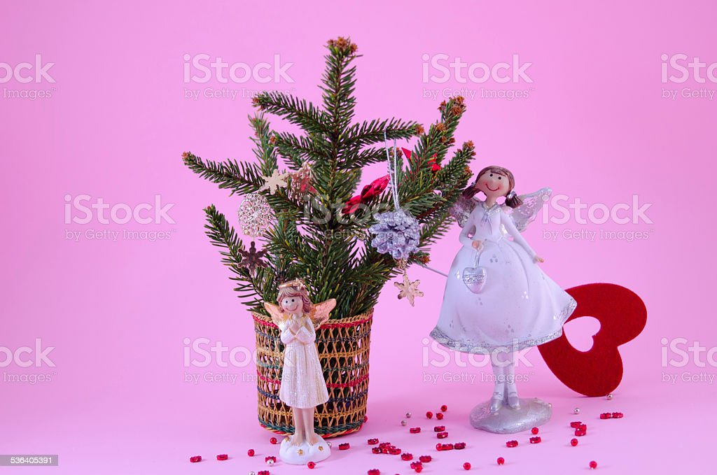 Two angel figurines on pink background royalty-free stock photo