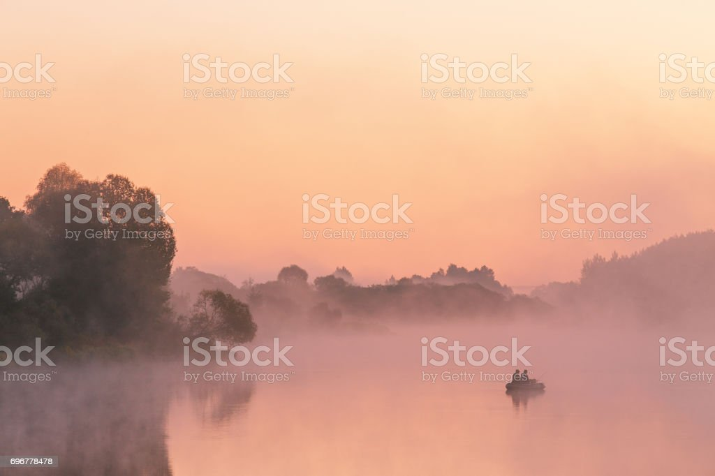Two anglers on a boat enjoys fishing on a beautiful morning. stock photo