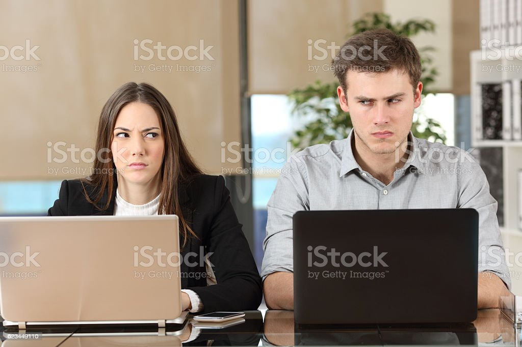 Front view of two angry businesspeople using computers disputing at...