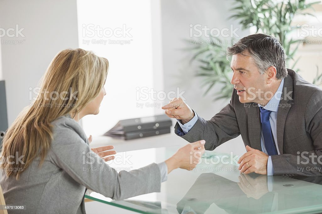 Two angry co workers arguing in an office stock photo