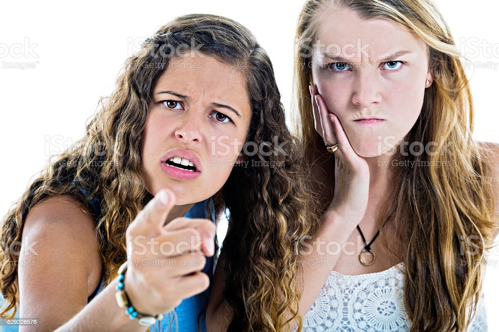Two angry girls gesture and grimace in disgust and disapproval stock photo