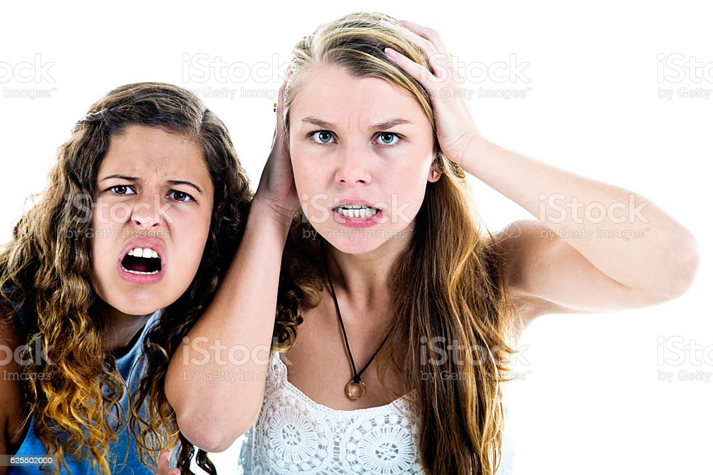 Two angry young women grimacing, shocked and outraged stock photo
