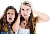 Two angry young women grimacing, shocked and outraged