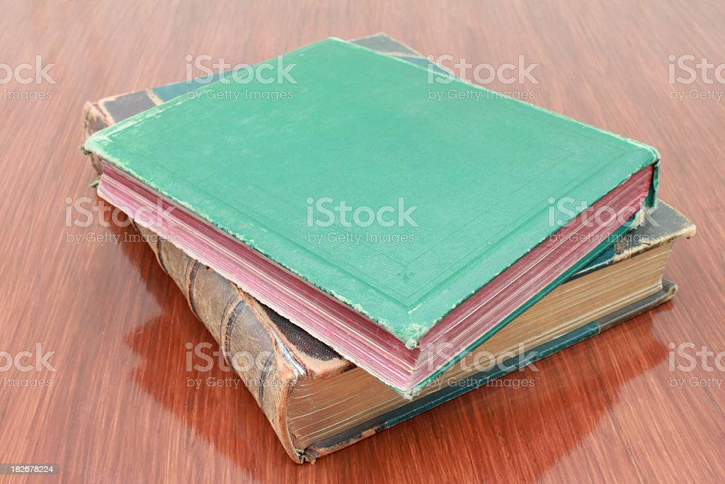 two antique leather-bound  cloth-bound books on polished table stock photo