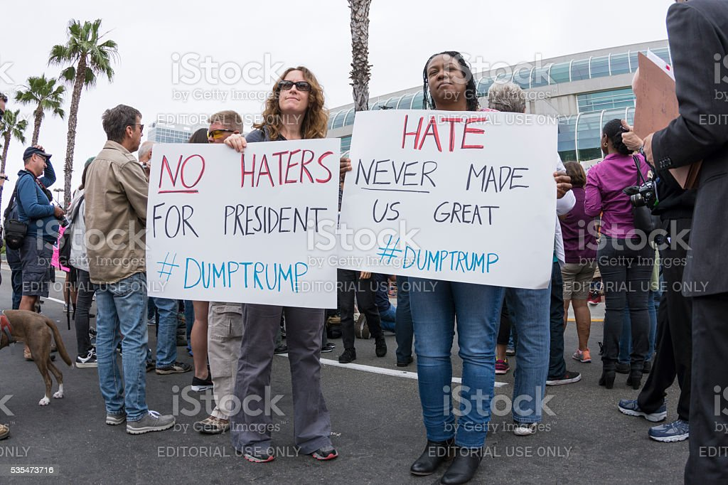 Two anti-Trump protesters with anti-hate signs stock photo