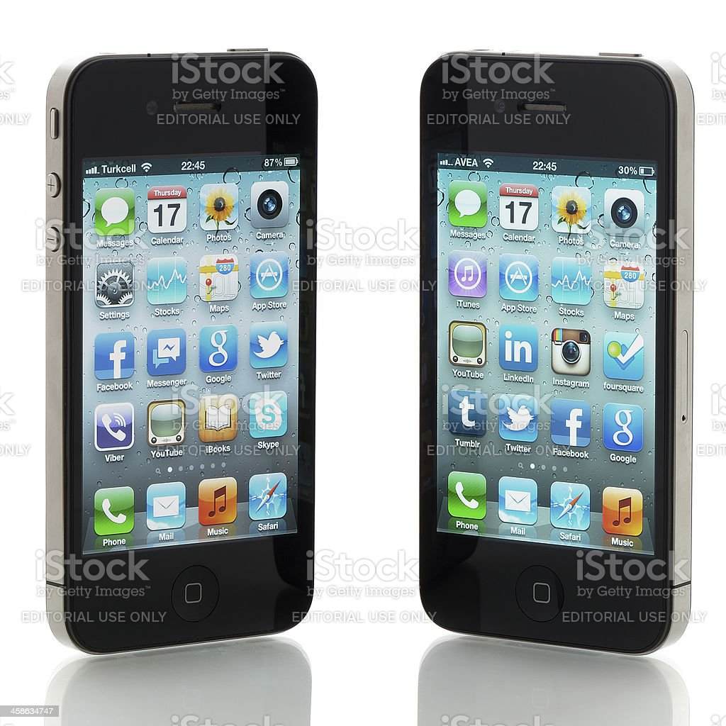 Two Apple iPhone 4s displaying homescreen royalty-free stock photo