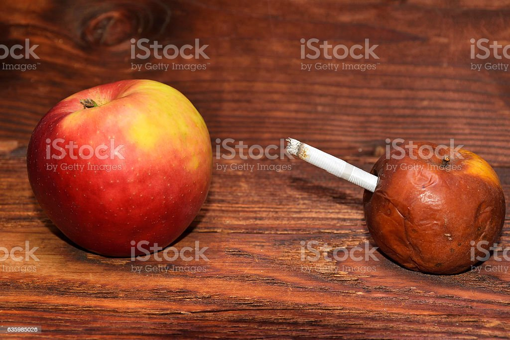 two apples and a cigarette in wood background. smoke kills stock photo