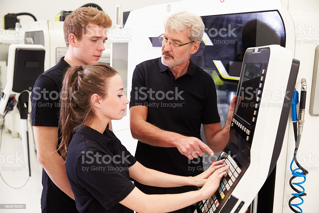 Two Apprentices Working With Engineer On CNC Machinery stock photo