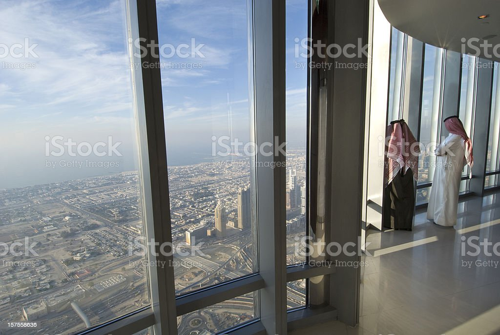 Two Arab men looking over Dubai from the Burj Khalifa stock photo