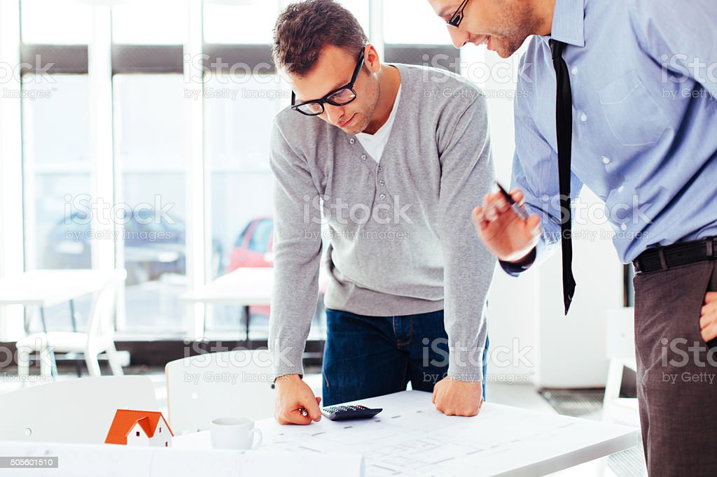 Two architects discussing a blueprint stock photo