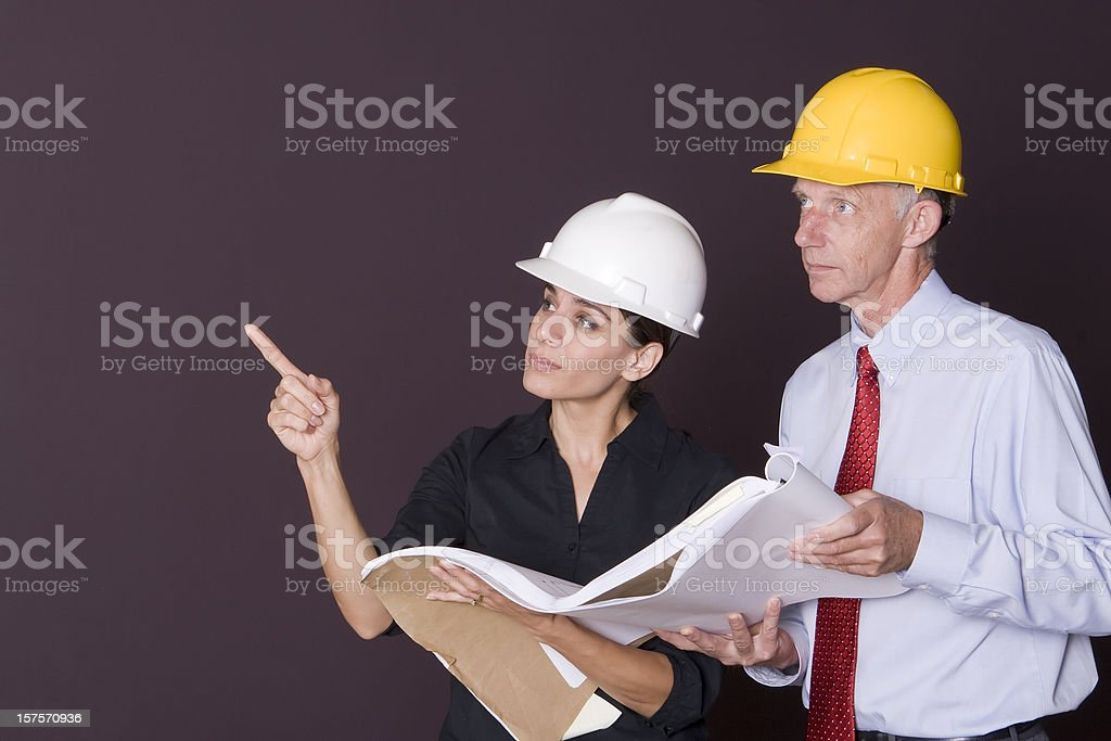 Two architects in hardhats examining blueprints royalty-free stock photo
