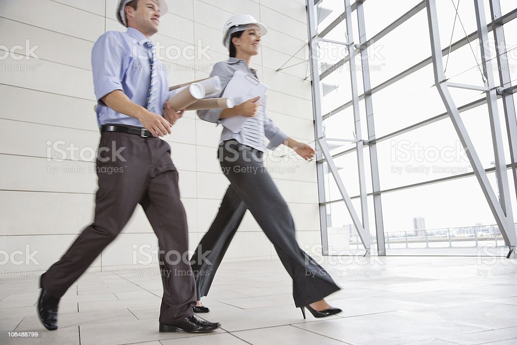 Two architects walking in hurry with hardhats and rolled blue prints royalty-free stock photo